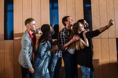 Les jeunes heureux faisant le selfie dans la chambre près du mur en bois Photos stock