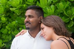 Les jeunes heureux mélangent les couples emballés sur le fond vert Image stock