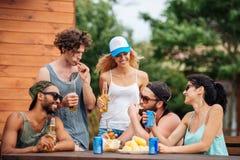 Les jeunes heureux mangeant et buvant dehors Photo stock