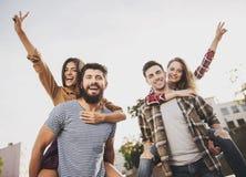 Les jeunes heureux ont l'amusement dehors en automne photo libre de droits