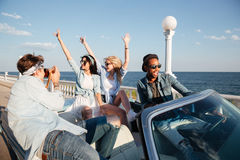 Les jeunes heureux prenant des photos et ayant l'amusement dans le cabriolet Photographie stock libre de droits