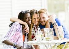Les jeunes heureux riant un être heureux à une table Image libre de droits