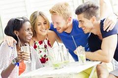 Les jeunes heureux riant un être heureux à une table Photo libre de droits