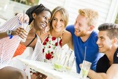 Les jeunes heureux riant un être heureux à une table Images stock