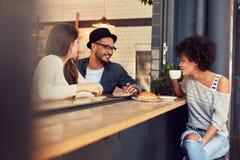 Les jeunes heureux s'asseyant dans un café Photographie stock