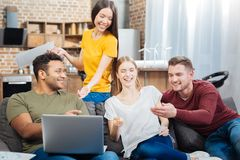 Les jeunes heureux s'asseyant sur le sofa et riant tout en observant des vidéos Image libre de droits