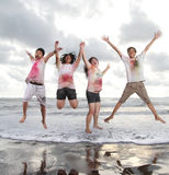 Les jeunes heureux sautant dans une plage en été avec le mouvement lent et le concept trouble Photo libre de droits
