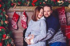 Les jeunes heureux se donnent des cadeaux par la cheminée près de l'arbre de Noël Image stock