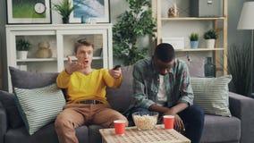 Les jeunes hommes émotifs observent le jeu à la TV tenant la déception négative alors de expression à télécommande d'émotions et banque de vidéos