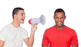 Les jeunes hommes crie à son ami fâché par un mégaphone Photos stock