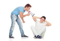 Les jeunes hommes crie à son ami par un mégaphone Images stock
