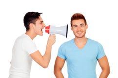 Les jeunes hommes crie à son ami par un mégaphone Photos stock