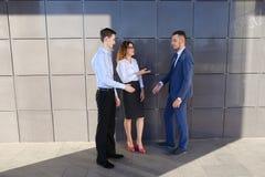Les jeunes hommes d'affaires attirants d'adultes, étudiants rencontrés et discutent Photographie stock