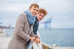 Les jeunes hommes, hommes d'affaires se tiennent sur le pilier Image libre de droits