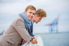 Les jeunes hommes, hommes d'affaires se tiennent sur le pilier Image stock