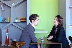 Les jeunes hommes et les femmes communiquent et partagent des secrets, se reposant dedans dedans Photographie stock