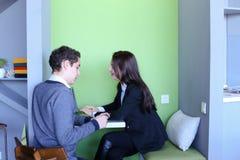 Les jeunes hommes et les femmes communiquent et partagent des secrets, se reposant dedans dedans Image stock