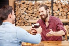 Les jeunes hommes gais se reposent dans le bar Photo stock