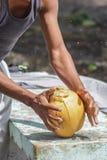 Les jeunes hommes latins ouvre une noix de coco photo stock