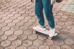 Les jeunes jambes de planchiste dans des collants de jeans et des espadrilles blanches patinent Photos stock