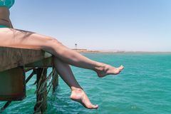 Les jeunes jambes femelles pendent de la jetée au-dessus de l'eau de mer Photographie stock