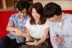 Les jeunes japonais appréciant le contenu d'Internet avec le dispositif de comprimé Images libres de droits