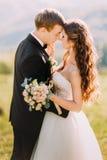 Les jeunes jeunes mariés de nouveaux mariés avec le frottage de bouquet de fleur flairent dehors Images stock