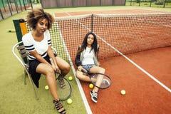 Les jeunes jolies amies accrochant sur le court de tennis, façonnent le butin habillé élégant, sourire heureux de meilleurs amis  Images stock