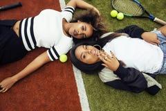 Les jeunes jolies amies accrochant sur le court de tennis, façonnent le butin habillé élégant, sourire heureux de meilleurs amis  Photos stock