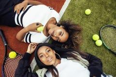 Les jeunes jolies amies accrochant sur le court de tennis, façonnent le butin habillé élégant, sourire heureux de meilleurs amis  Photos libres de droits