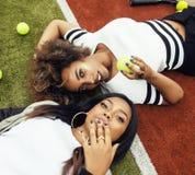 Les jeunes jolies amies accrochant sur le court de tennis, façonnent le butin habillé élégant, sourire heureux de meilleurs amis  Photographie stock