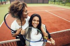 Les jeunes jolies amies accrochant sur le court de tennis, façonnent le butin habillé élégant, sourire heureux de meilleurs amis  Photo stock