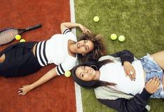 Les jeunes jolies amies accrochant sur le court de tennis, façonnent le butin habillé élégant, sourire heureux de meilleurs amis  Photo libre de droits