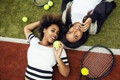 Les jeunes jolies amies accrochant sur le court de tennis, façonnent le butin habillé élégant, sourire heureux de meilleurs amis  Image libre de droits