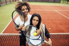 Les jeunes jolies amies accrochant sur le court de tennis, façonnent le butin habillé élégant, sourire heureux de meilleurs amis  Images libres de droits