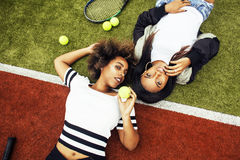 Les jeunes jolies amies accrochant sur le court de tennis, façonnent le butin habillé élégant, sourire heureux de meilleurs amis  Photographie stock libre de droits
