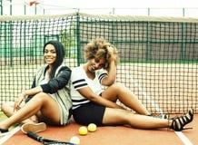 Les jeunes jolies amies accrochant sur le court de tennis, fa?onnent le butin habill? ?l?gant, sourire heureux de meilleurs amis  images stock