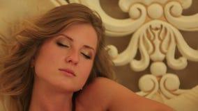 Les jeunes jolies femmes songeuses se situent dans l'american national standard de lit touche ses cheveux banque de vidéos