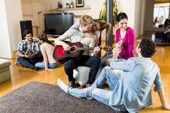 Les jeunes jouant la guitare et ayant une partie dans la maison Image stock