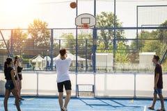 Les jeunes jouant le basket-ball sur le terrain de jeu Images stock
