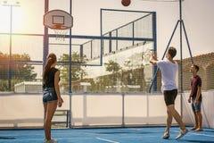 Les jeunes jouant le basket-ball sur le terrain de jeu Photo stock