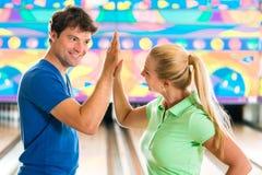 Les jeunes jouant le bowling et ayant l'amusement Photos stock