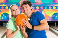 Les jeunes jouant le bowling et ayant l'amusement Photos libres de droits
