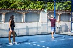 Les jeunes jouant le tennis sur le terrain de jeu Photographie stock libre de droits