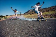 Les jeunes longboarding en bas de la route Images libres de droits