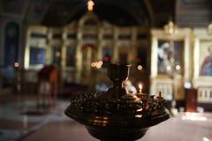 Les jeunes lumières adolescentes par bougie d'église pour la méditation et prient Image stock