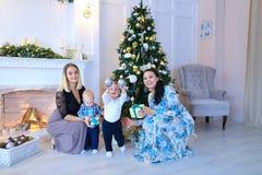 Les jeunes mères posent et souriant avec leurs petits enfants près de W Image libre de droits