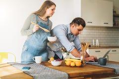 Les jeunes ménage dans la cuisine L'homme tient la table proche et utilise l'ordinateur portable, épouse enceinte se tient à côté Image stock