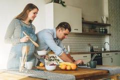 Les jeunes ménage dans la cuisine L'homme tient la table proche et utilise l'ordinateur portable, épouse enceinte se tient à côté Image libre de droits
