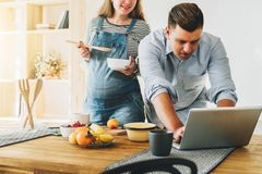 Les jeunes ménage dans la cuisine L'homme tient la table proche et utilise l'ordinateur portable, épouse enceinte se tient à côté Photographie stock libre de droits